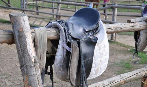 English horse saddle on a fence