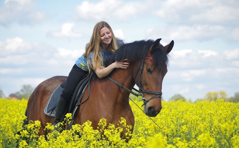 Girl hugging and riding her horse