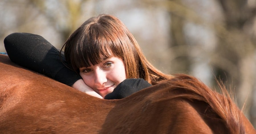 Girl resting and smiling on a horse's back