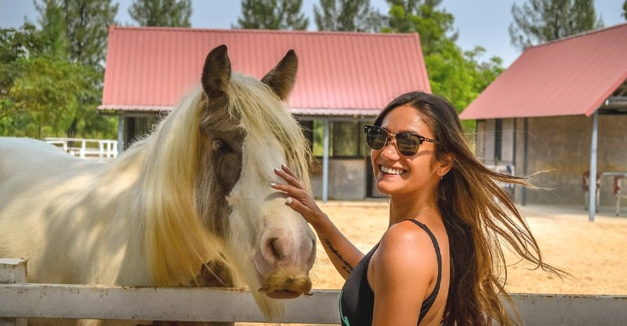 Girl smiling while she strokes a horse