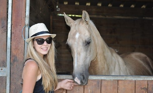 Girl with her horse outside it's stall