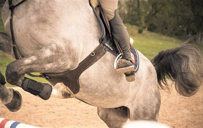 Horse rider using the ophena magnetic safety stirrups while jumping