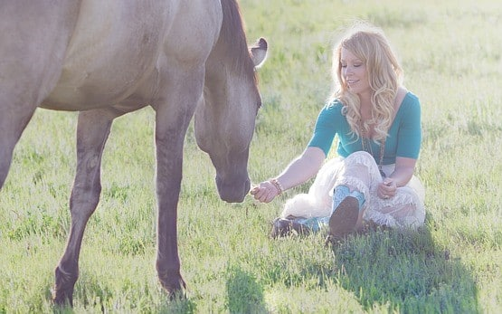 Girl rewarding her horse with a treat in a field
