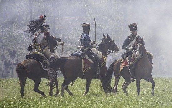 Horses being ridden into a battle being used for war