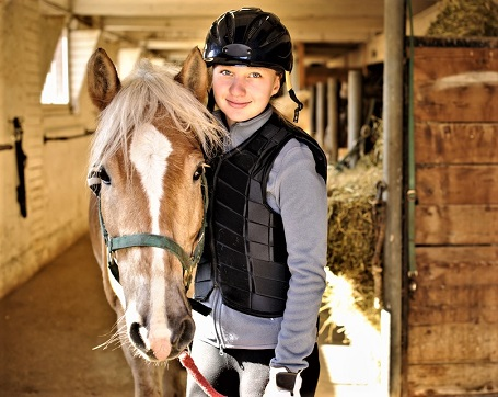 Horse and girl with horse riding safety equipment