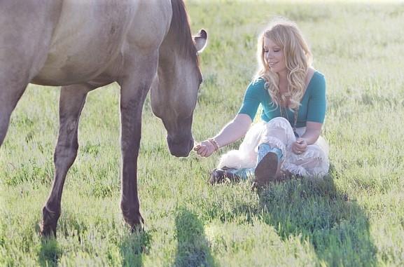 Woman rewarding a horse she owns