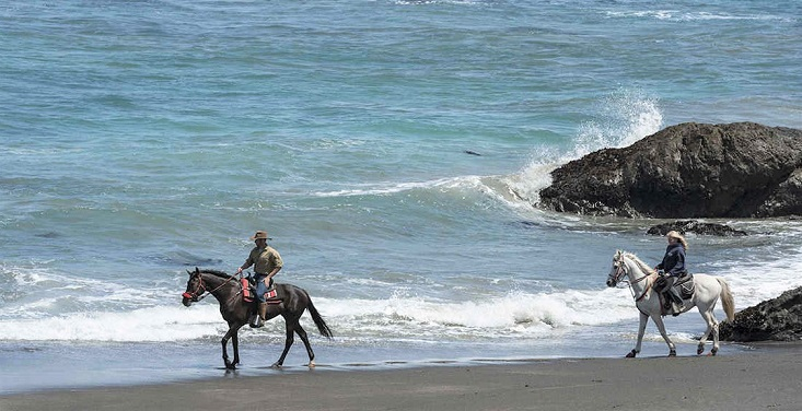Two horse riders on the Ten Mile Beach in California