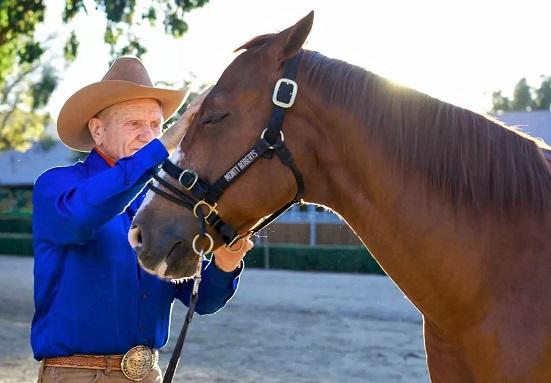 Monty Roberts stroking a horse