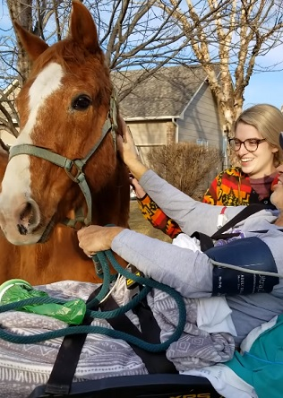 Cowboy in a hospital bed stroking his horse outside his house