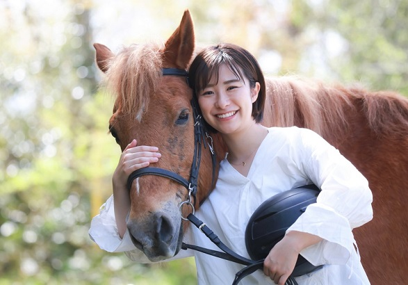 Woman hugging a horse while looking at the camera